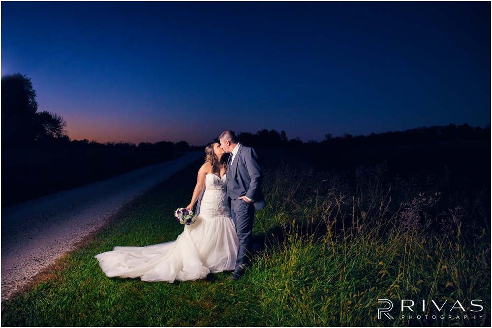 elegant fall wedding buffalo lodge | A photo of a bride and groom kissing at dusk at The Buffalo Lodge.