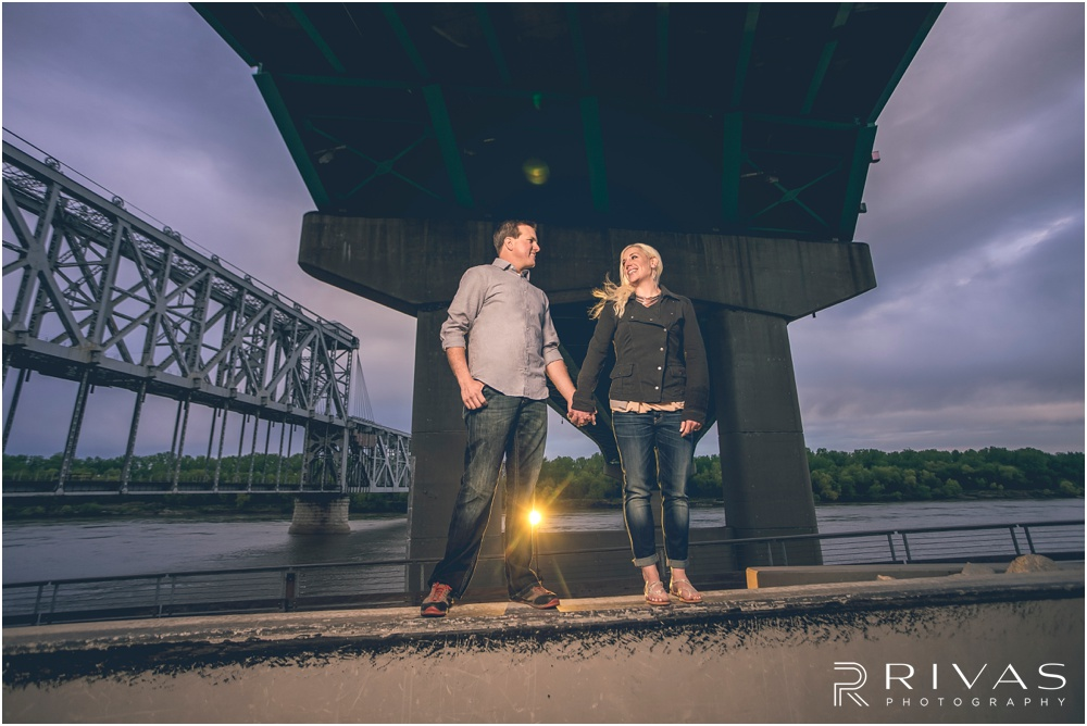 mini engagement session | Photo of an engaged couple holding hands under the bridges at Berkley River Front Park in Kansas City.