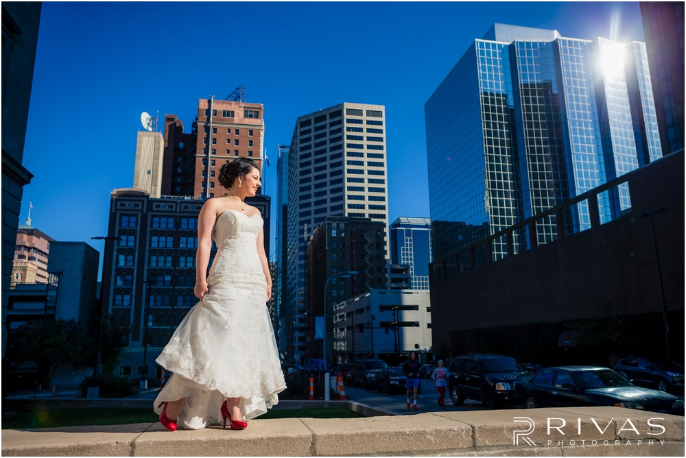 KC Winter Wedding | A picture of a bride showing off her red shoes and wedding gown against the Kansas City skyline.