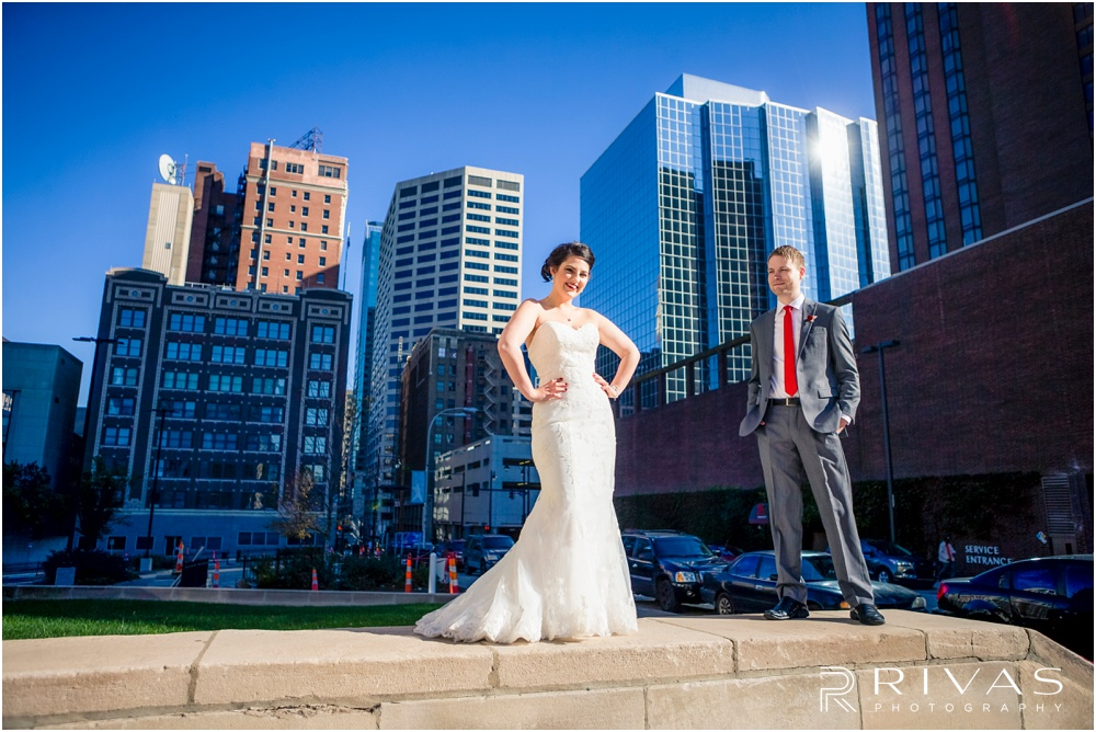 KC Winter Wedding | A picture of a bride and groom standing on a wall in front of the Kansas City skyline.