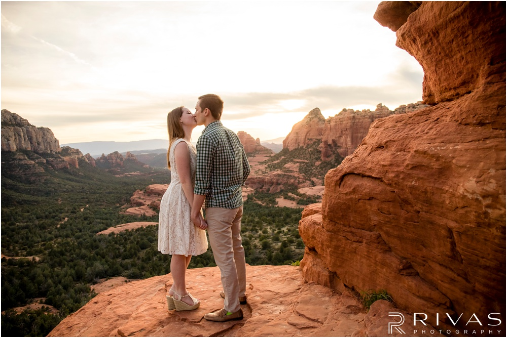 Merry-Go-Round Rock Engagement Session | Picture of an engaged couple kissing standing on a cliff at Merry-Go-Round Rock in Sedona.