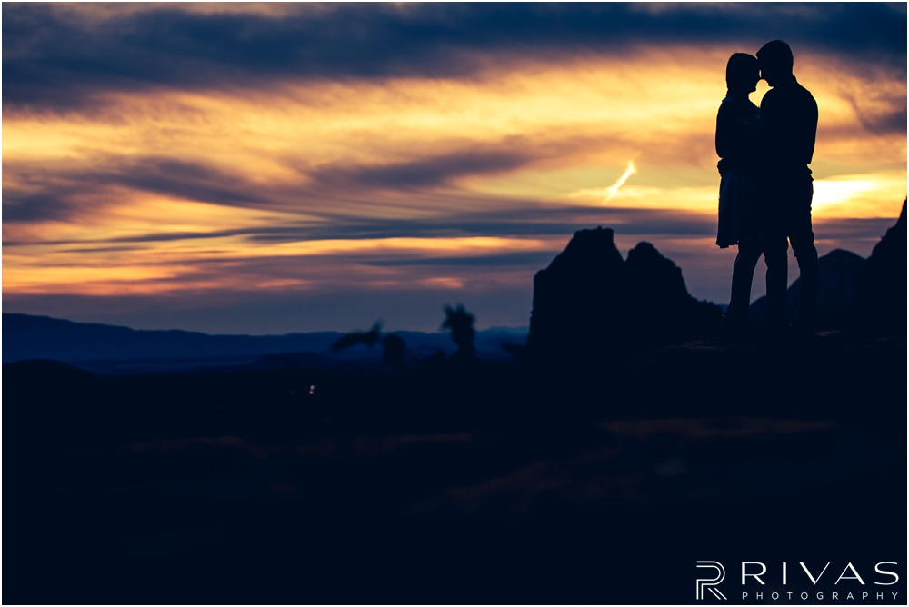 Merry-Go-Round Rock Engagement Session | Silhouette photo of an engaged couple standing on Merry-Go-Round Rock at sunset in Sedona.