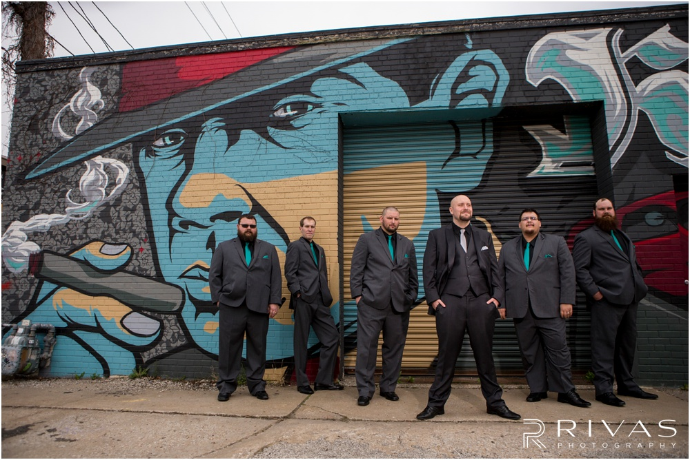 Vibrant Spring Wedding at The Guild | A picture of a groom and his groomsmen standing in front of a turquoise mural in Kansas City's Crossroads District.