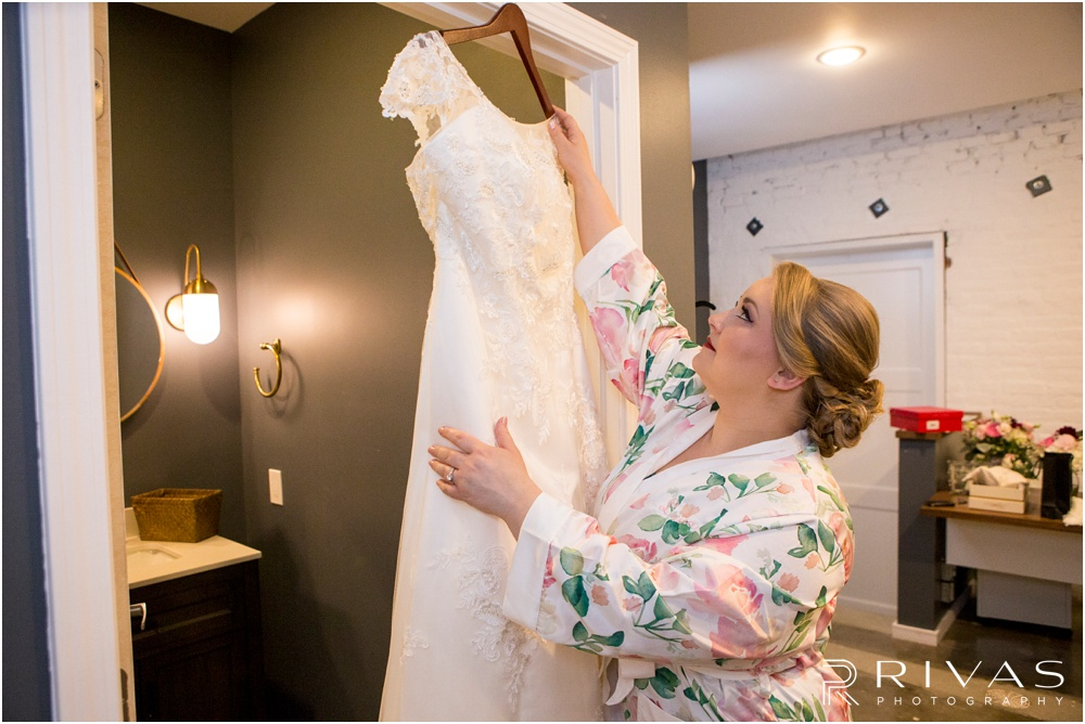 Vibrant Spring Wedding at The Guild | A picture of a bride dressed in a white floral robe reaching up to grab her wedding gown in the bridal suite at The Guild KC.