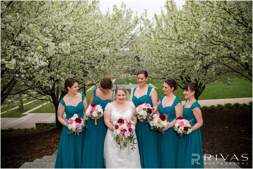 Vibrant Spring Wedding at The Guild | Three candid pictures of a bride and her bridesmaids underneath flowering trees at Ilus Davis Park in Kansas City.