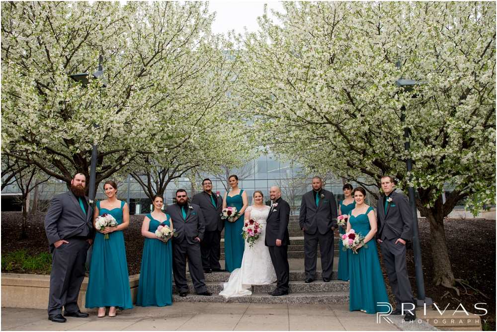 Vibrant Spring Wedding at The Guild | Formal picture of a bride and groom with their wedding party underneath flowering trees at Ilus Davis Park in Kansas City.