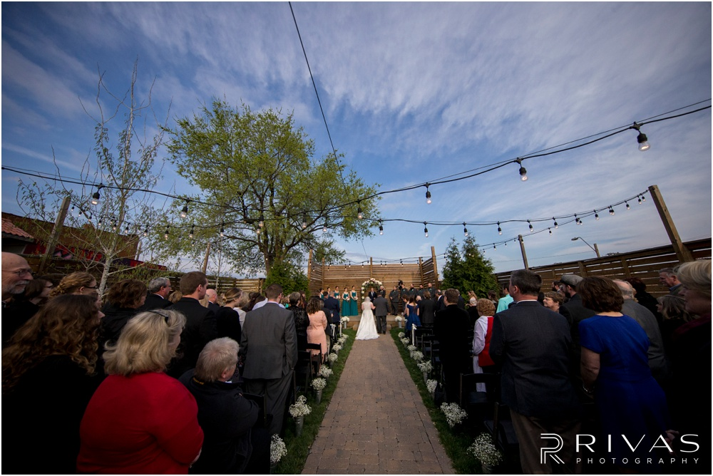 Vibrant Spring Wedding at The Guild | Picture of a bride's father walking her down the aisle in the courtyard at The Guild KC.