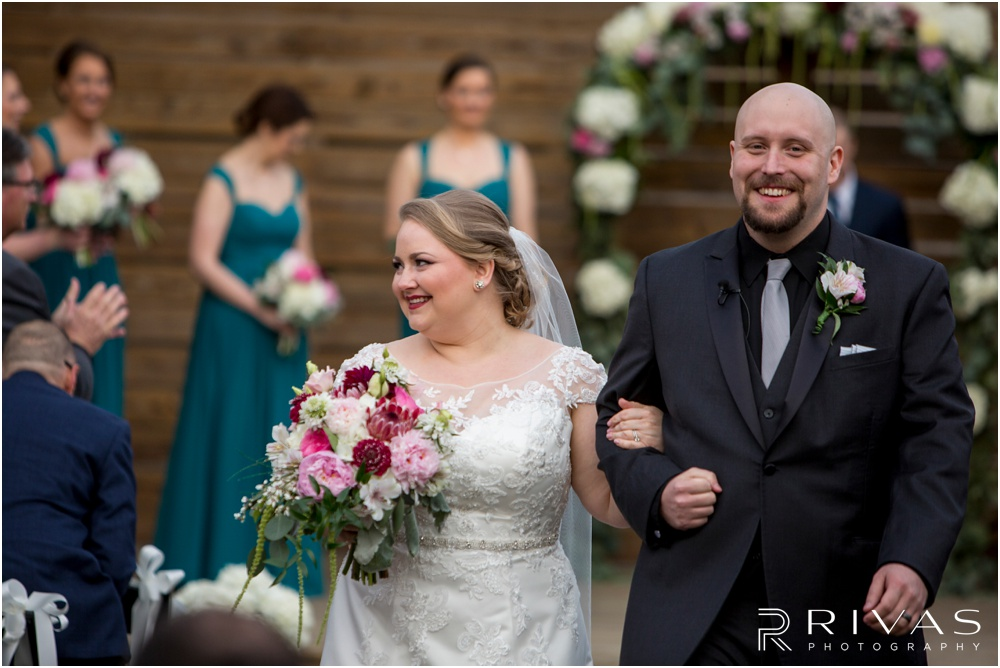 Vibrant Spring Wedding at The Guild | A picture of a bride and groom walking back down the aisle after their wedding ceremony in the courtyard at The Guild KC.
