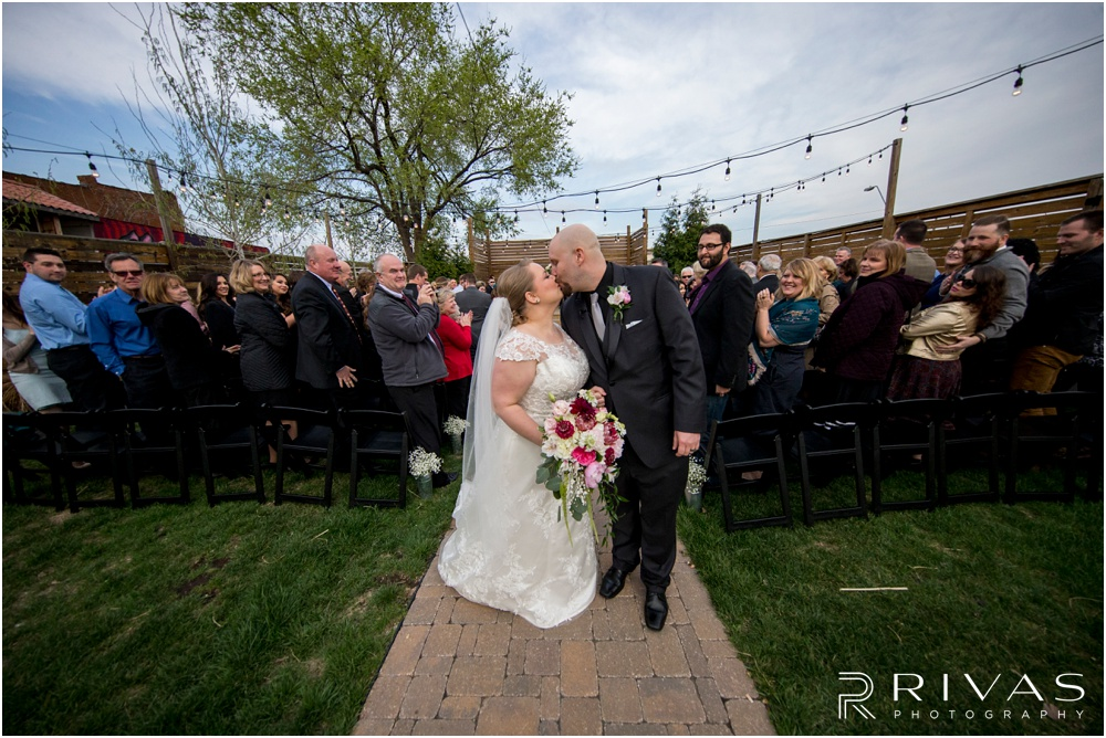 Vibrant Spring Wedding at The Guild | A picture of a bride and groom sharing a kiss at the end of the aisle after their wedding ceremony in the courtyard at The Guild KC.