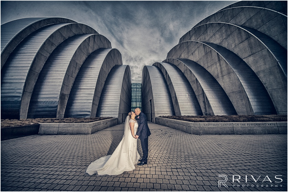 Vibrant Spring Wedding at The Guild | A dramatic picture of a bride and groom kissing in front of The Kauffman Center for Performing Arts in Kansas City.
