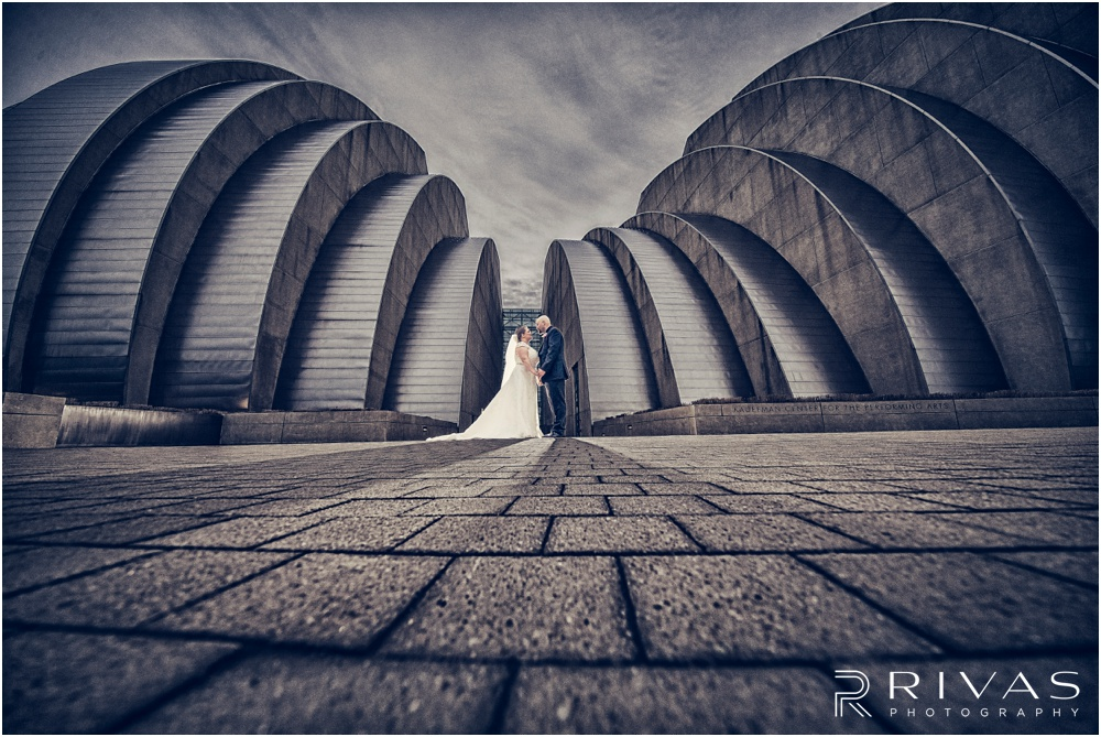 Vibrant Spring Wedding at The Guild | A dramatic picture of a bride and groom holding hands in front of The Kauffman Center for Performing Arts in Kansas City.