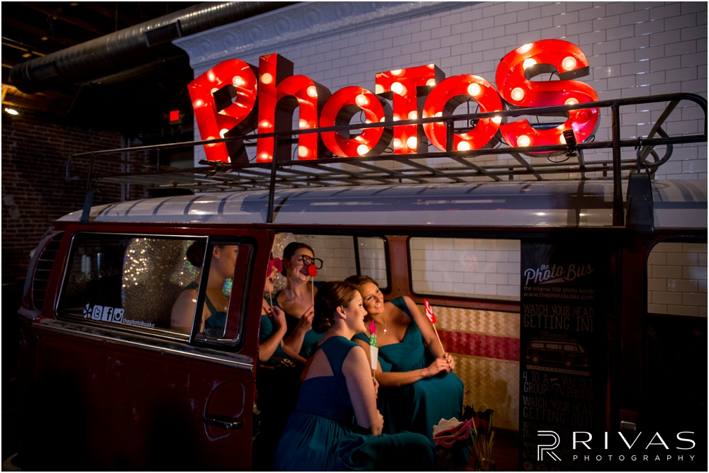 Vibrant Spring Wedding at The Guild | A candid picture of bridesmaids taking pictures in The Photo Bus at The Guild KC.