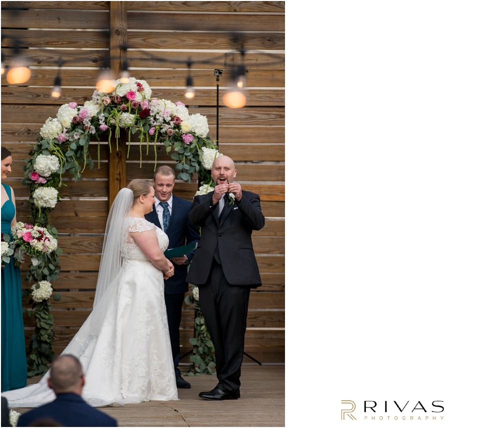 Vibrant Spring Wedding at The Guild | Candid photo of a groom showing off his bride's wedding ring during their wedding ceremony in the courtyard at The Guild KC.