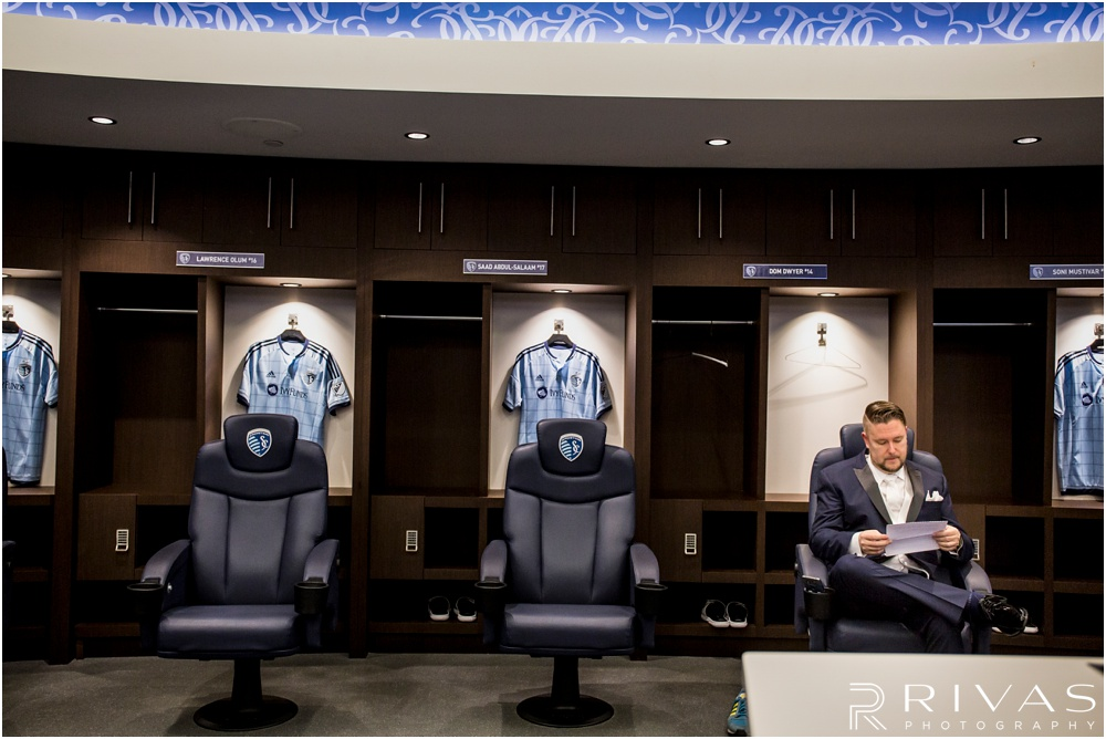 children's mercy park winter wedding | A picture of a groom reading a letter from his bride while sitting in a plush locker room chair.