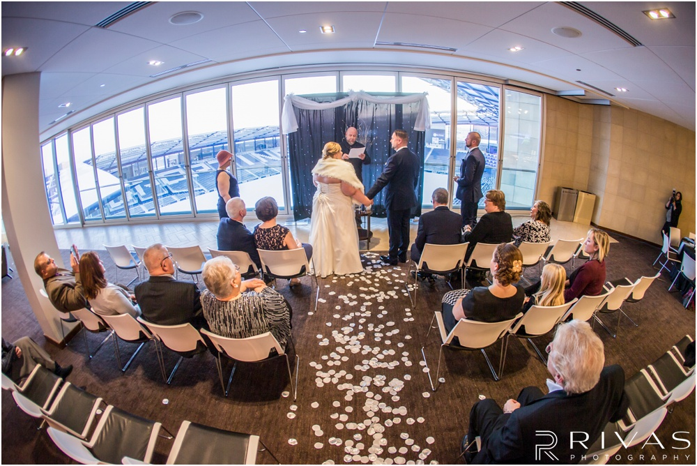 children's mercy park winter wedding | A picture from the back of the ceremony space showing the bride and groom saying their vows.