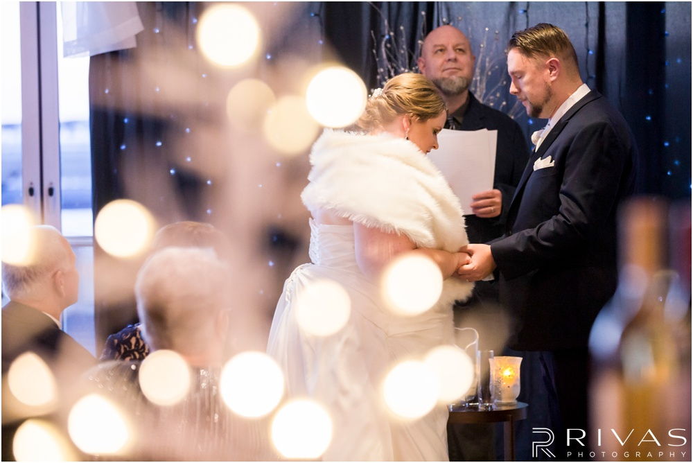 children's mercy park winter wedding | An intimate image of a bride and groom praying during their wedding ceremony at Children's Mercy Park.