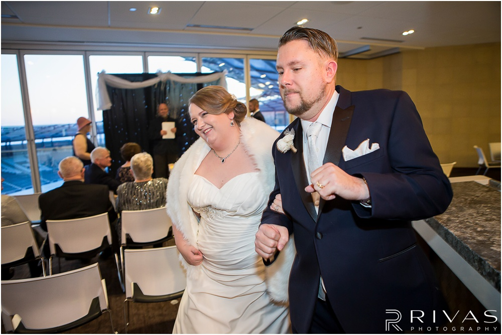 children's mercy park winter wedding | A candid image of a bride and groom celebrating as they walk down the aisle after their wedding ceremony.