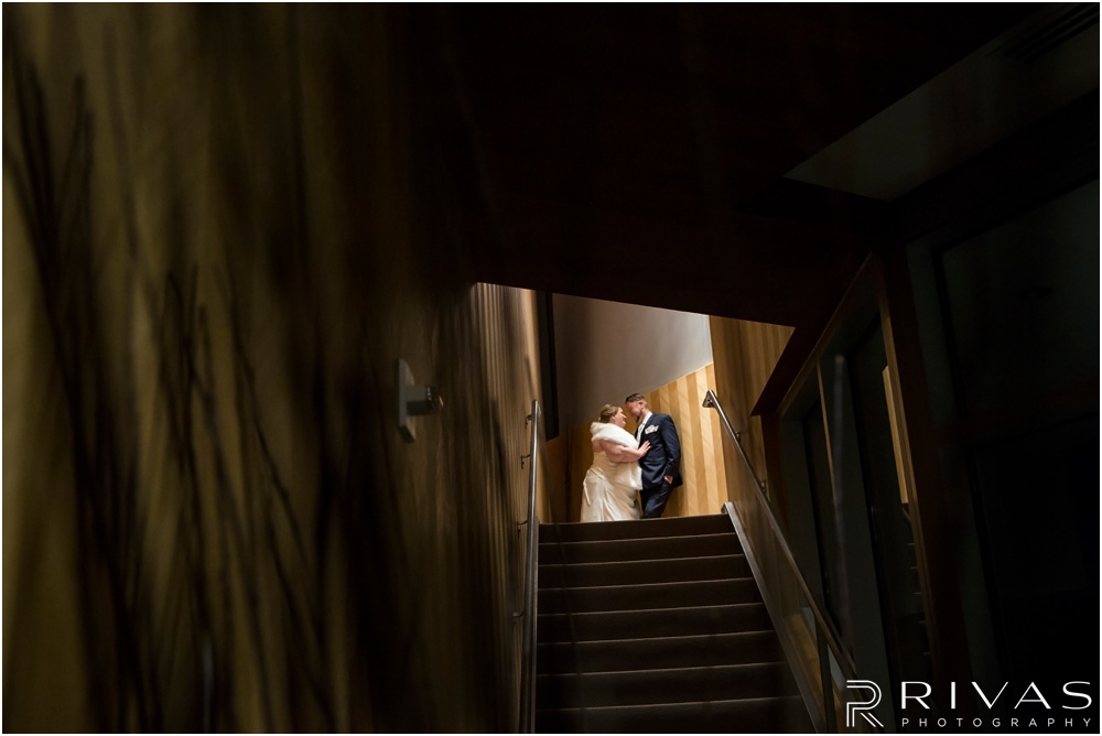 children's mercy park winter wedding | A photo of a couple embracing at the top of a flight of stairs after their wedding ceremony.