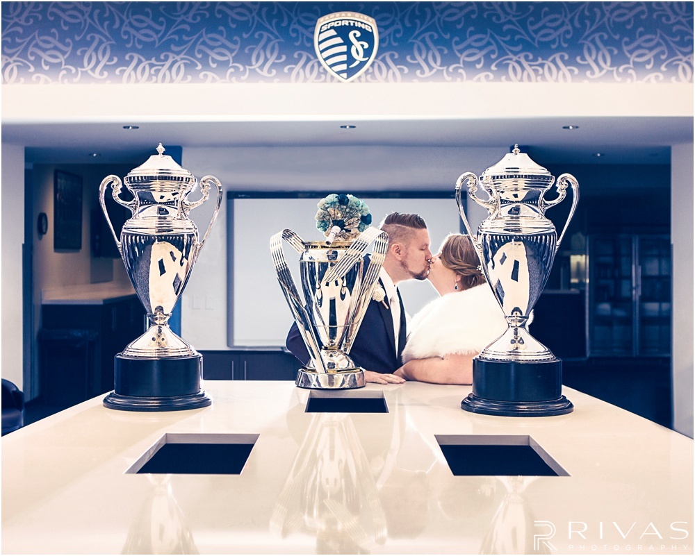children's mercy park winter wedding | A photo of a bride and groom sharing a kiss in the Sporting KC locker room with championship trophies.