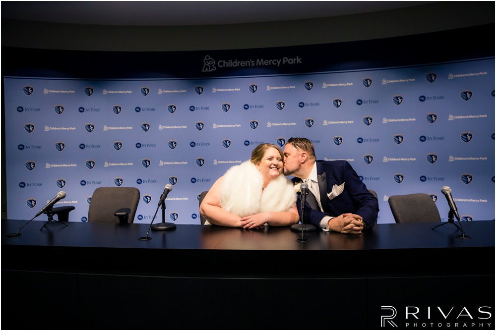 children's mercy park winter wedding | A picture of a bride and groom sitting at the interview desk in the media room of Children's Mercy Park.