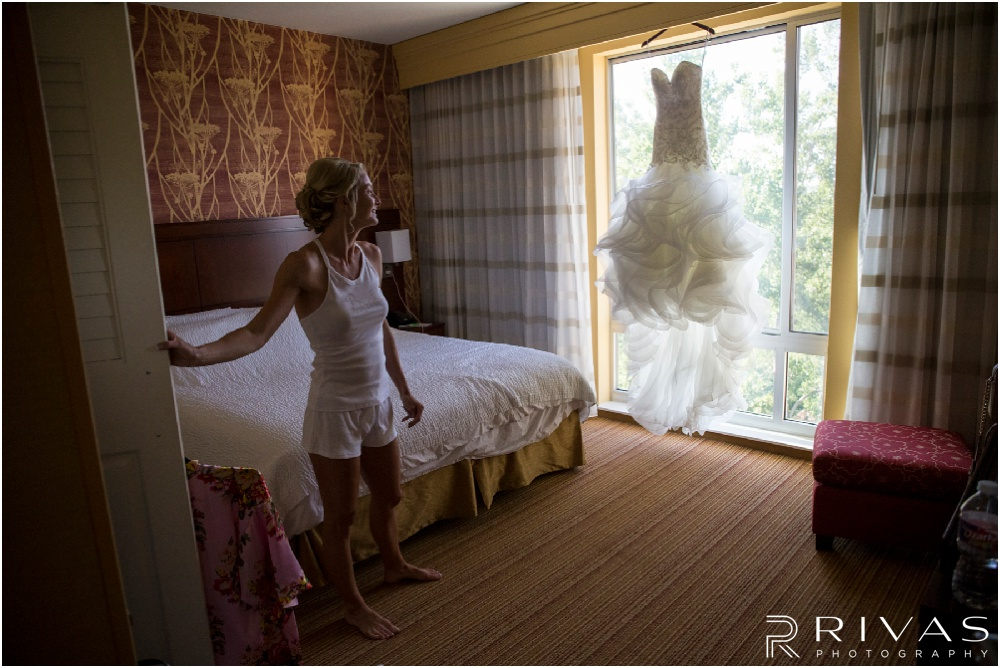 Wedding Day Timeline | Photo of a bride looking at her wedding dress hanging in the window of a hotel on her wedding day.