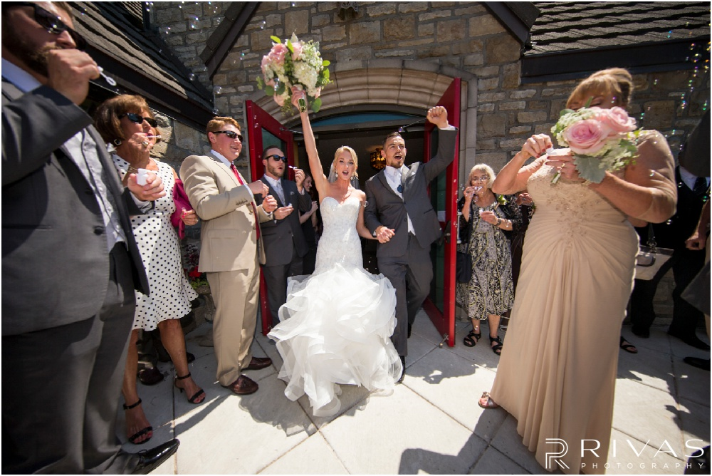Wedding Day Timeline | A bride and groom exiting a church just after their ceremony while friends and family blow bubbles at them.