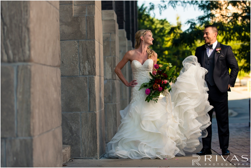 Garment House Styled Bridal Shoot | An image of a bride and groom outside The Garment House in downtown Kansas City holding Hitched flowers.
