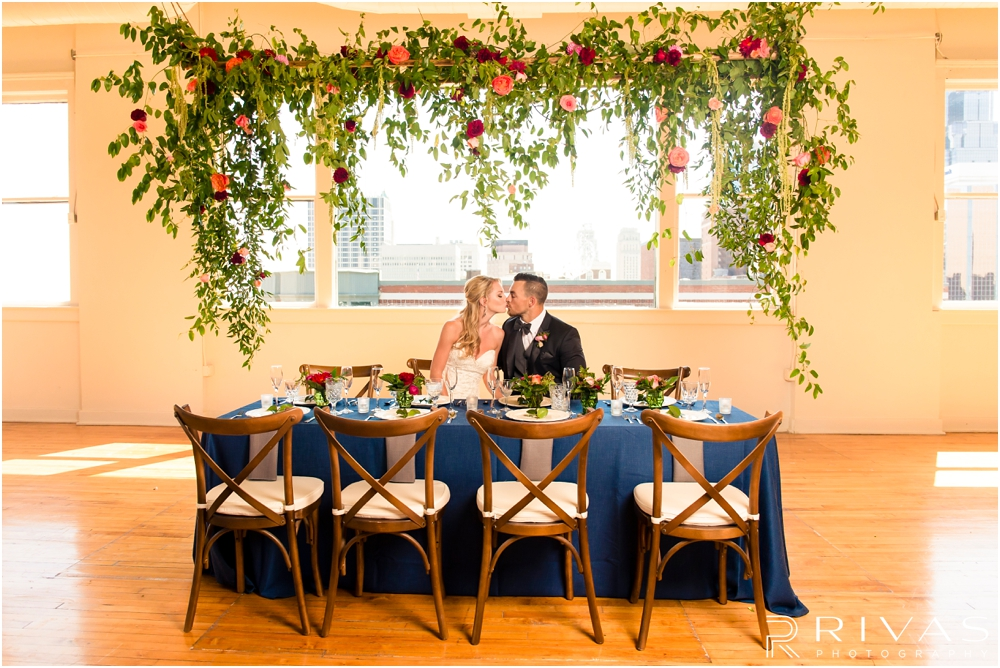 Garment House Styled Bridal Shoot | Two photos of a bride and groom sitting at a table in The Garment House underneath a greenery and rose filled garland styled by Hitched in Kansas City.