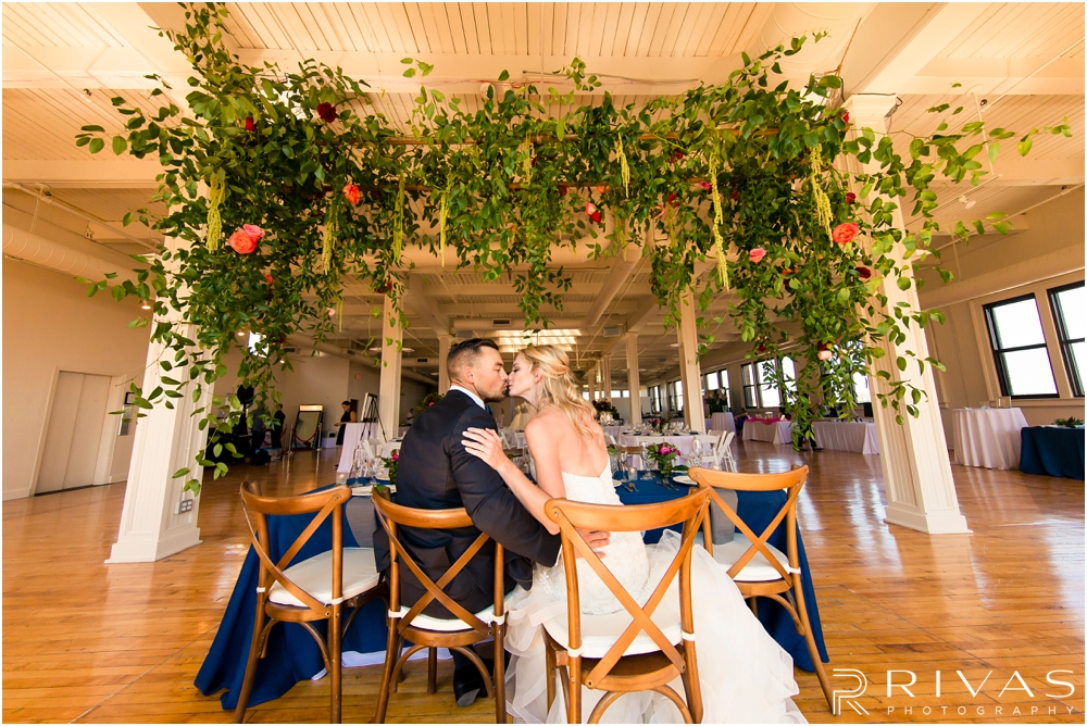 Garment House Styled Bridal Shoot | An image of a bride and groom sitting at a table in The Garment House underneath a greenery and rose filled garland styled by Hitched in Kansas City.