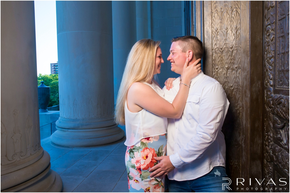 Nelson Atkins Summertime Engagement | An image of an engaged couple embracing and laughing with each other by the columns at The Nelson Atkins Museum of Art.
