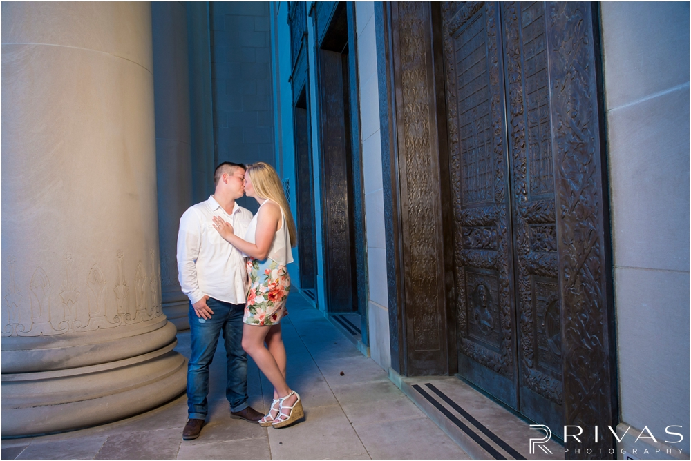 Nelson Atkins Summertime Engagement | An image of an engaged couple embracing  each other by the columns at The Nelson Atkins Museum of Art.