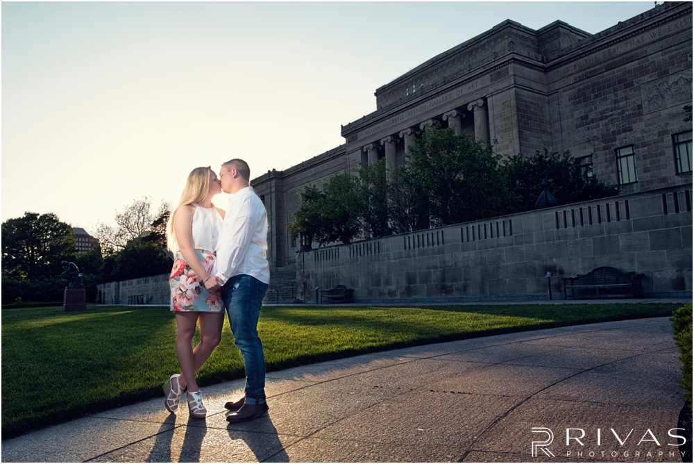 Nelson Atkins Summertime Engagement | An picture of an engaged couple kissing in front of the The Nelson Atkins Museum of Art.