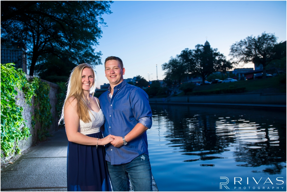 Nelson Atkins Summertime Engagement | An image of an engaged couple holding hands and smiling at the camera while standing alongside Brush Creek just south of the Kansas City Country Club Plaza.