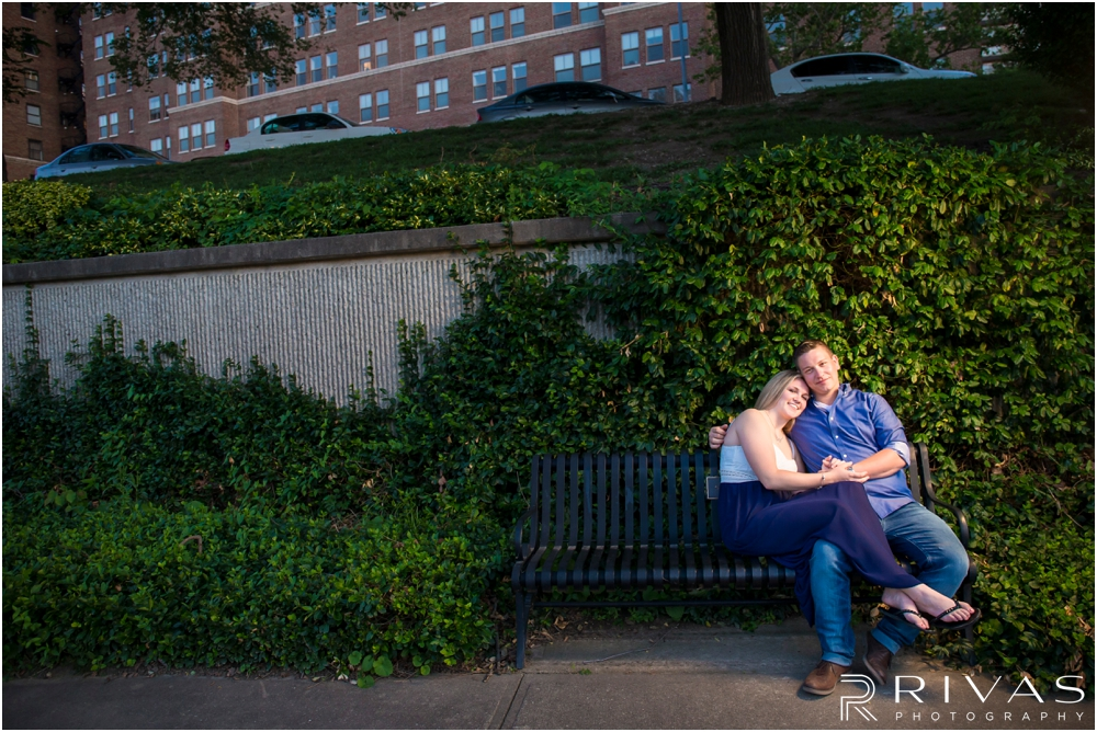 Nelson Atkins Summertime Engagement | A photo of an engaged couple sitting on a park bench in front of an ivy wall overlooking Brush Creek just south of the Kansas City Country Club Plaza.