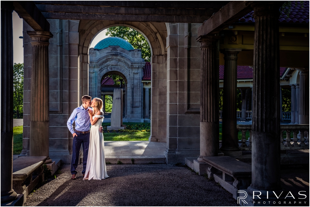 Romantic Spring Engagement Session | A dramatic picture of an engaged couple embracing and sharing a kiss at Kansas City's colonnade.