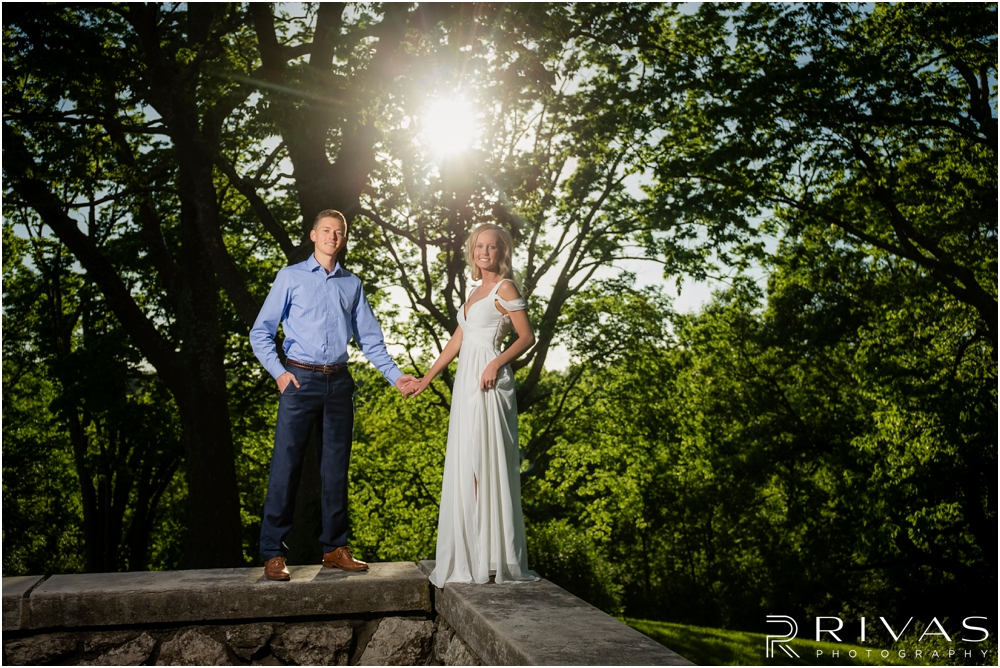 Romantic Spring Engagement Session | A picture of an engaged couple standing on a stone ledge holding hands in front of greenery at Kansas City's Colonnade.