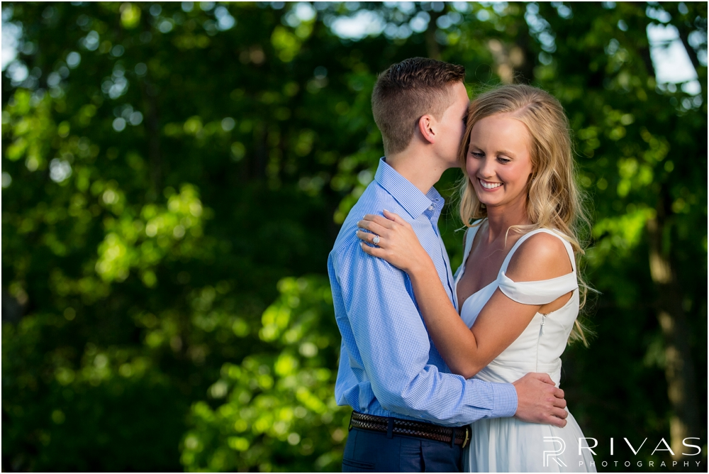 Romantic Spring Engagement Session | An image of an engaged couple embracing in front of greenery at Kansas City's Colonnade.