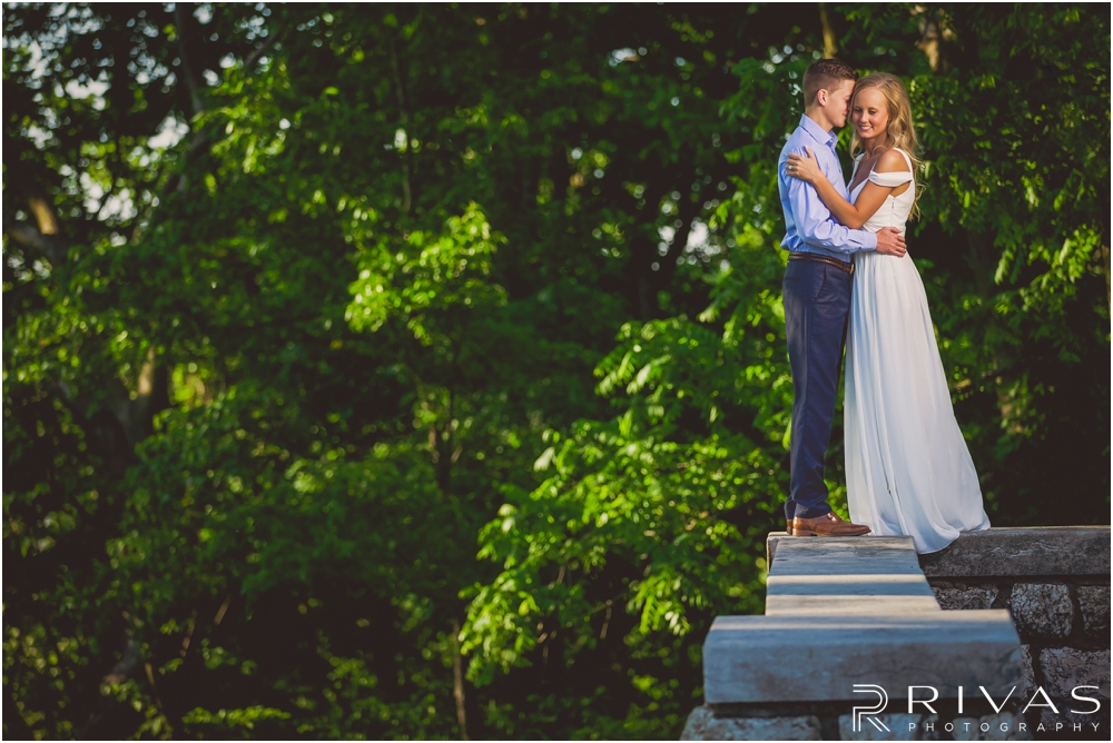 Romantic Spring Engagement Session | A picture of an engaged couple standing on a stone ledge embracing in front of greenery at Kansas City's Colonnade.