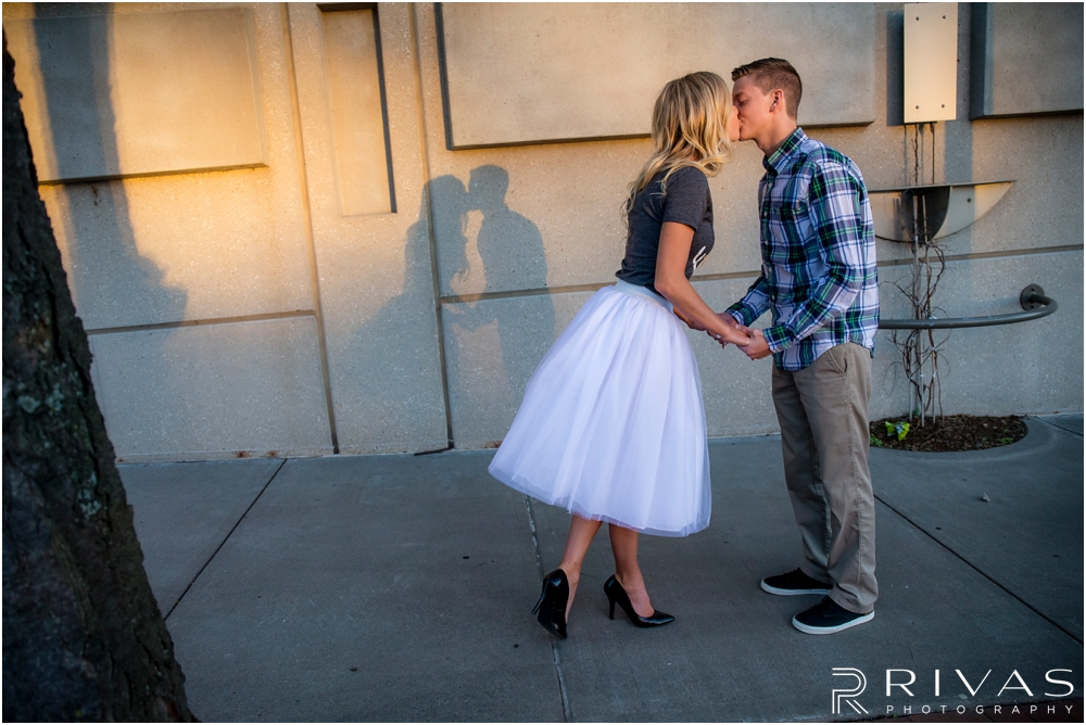Romantic Spring Engagement Session | A portrait of an engaged couple kissing on the streets of downtown Kansas City with their shadows in the background.