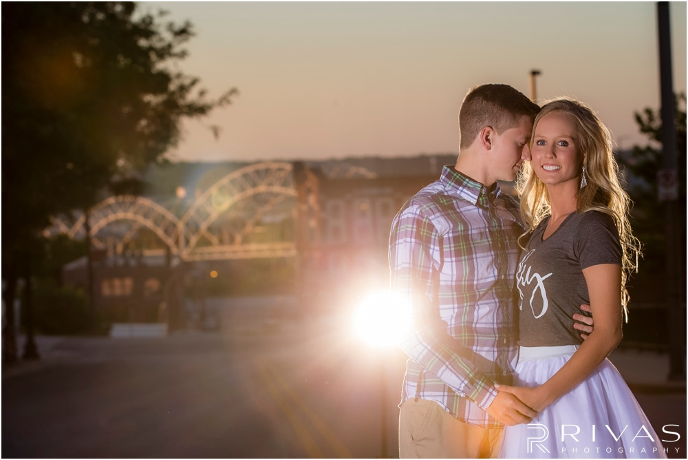 romantic spring engagement session in KC | A photo of an engaged couple holding hands and snuggling in downtown Kansas City at sunset.