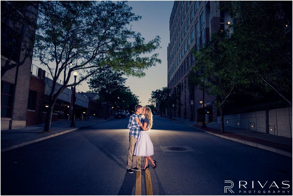 romantic spring engagement session in KC | A dramatic image of an engaged man dancing with his fiancé at sunset in the streets of downtown Kansas City.