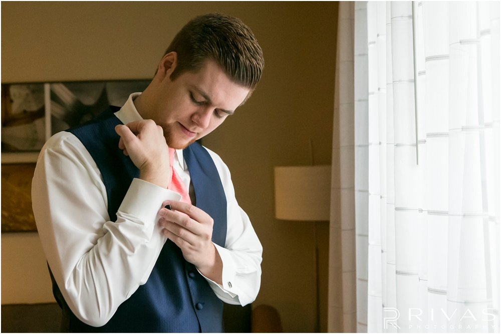 St. John the Evangelist Catholic Church Spring Wedding | An image of a groom putting on his cufflink standing in front of a window on his wedding day.
