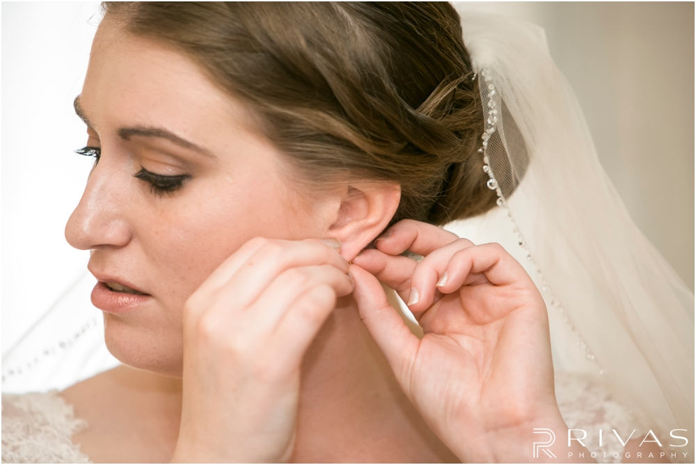 St. John the Evangelist Catholic Church Spring Wedding | A close-up image of a bride putting in her earrings on her wedding day.