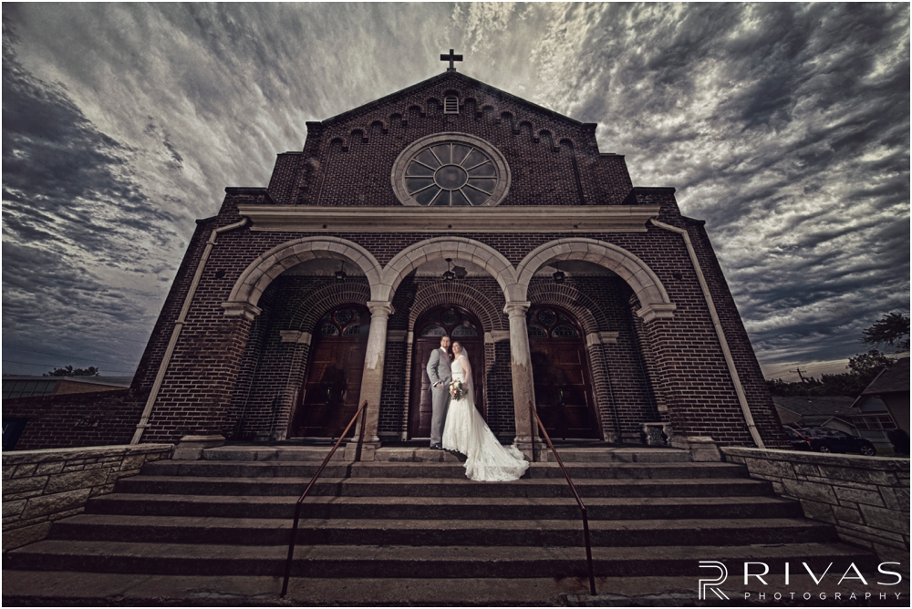 St. John the Evangelist Catholic Church Spring Wedding | A dramatic picture of a bride and groom embracing on the steps of St. John the Evangelist Catholic Church in Lawrence, KS.