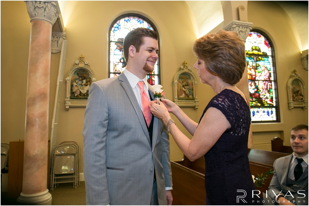 St. John the Evangelist Catholic Church Spring Wedding | A candid photo of a groom's mom pinning on his boutonniere just before his wedding ceremony.