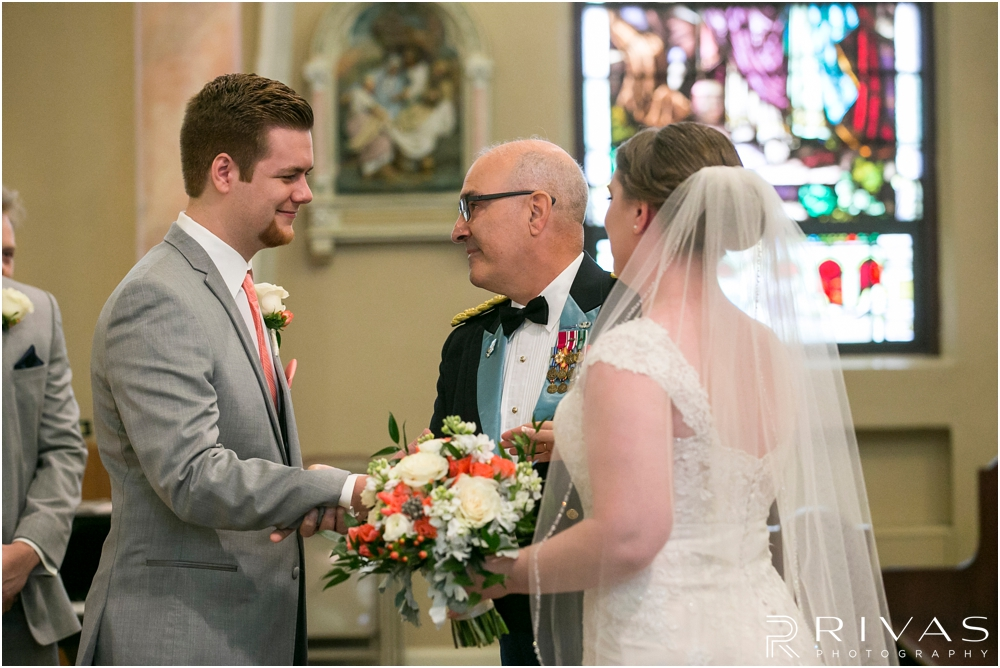 St. John the Evangelist Catholic Church Spring Wedding | A candid picture of a bride's father giving her away to her groom during their wedding ceremony.