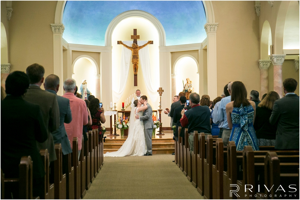 St. John the Evangelist Catholic Church Spring Wedding | A picture of a bride and groom sharing their first kiss during their wedding ceremony.