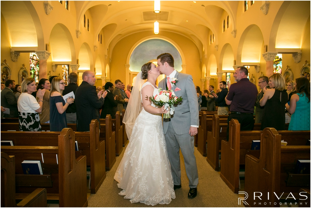 St. John the Evangelist Catholic Church Spring Wedding | A candid photo of a bride and groom sharing a kiss at the end of the aisle after their wedding ceremony.