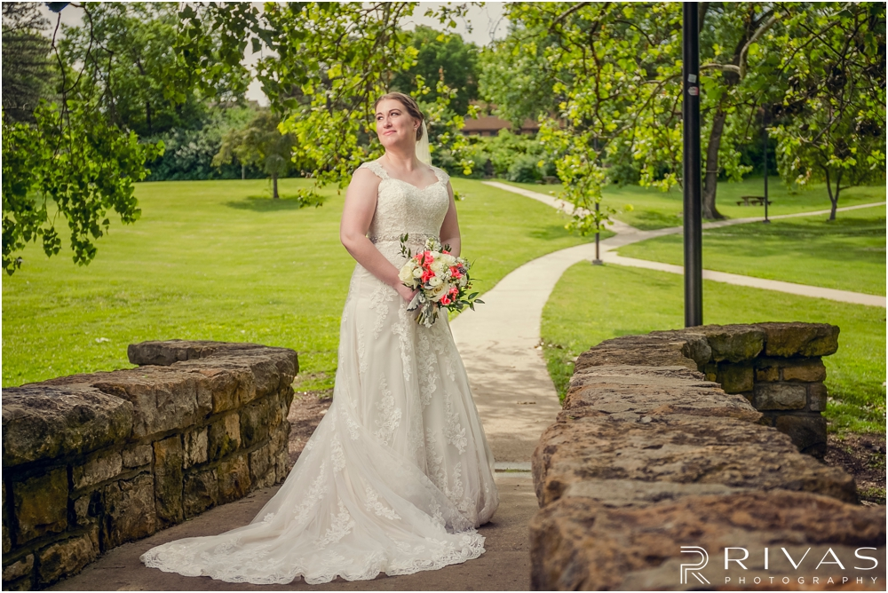St. John the Evangelist Catholic Church Spring Wedding | A portrait of a bride holding her bouquet standing on the stone bridge at Potter Lake in Lawrence, KS.