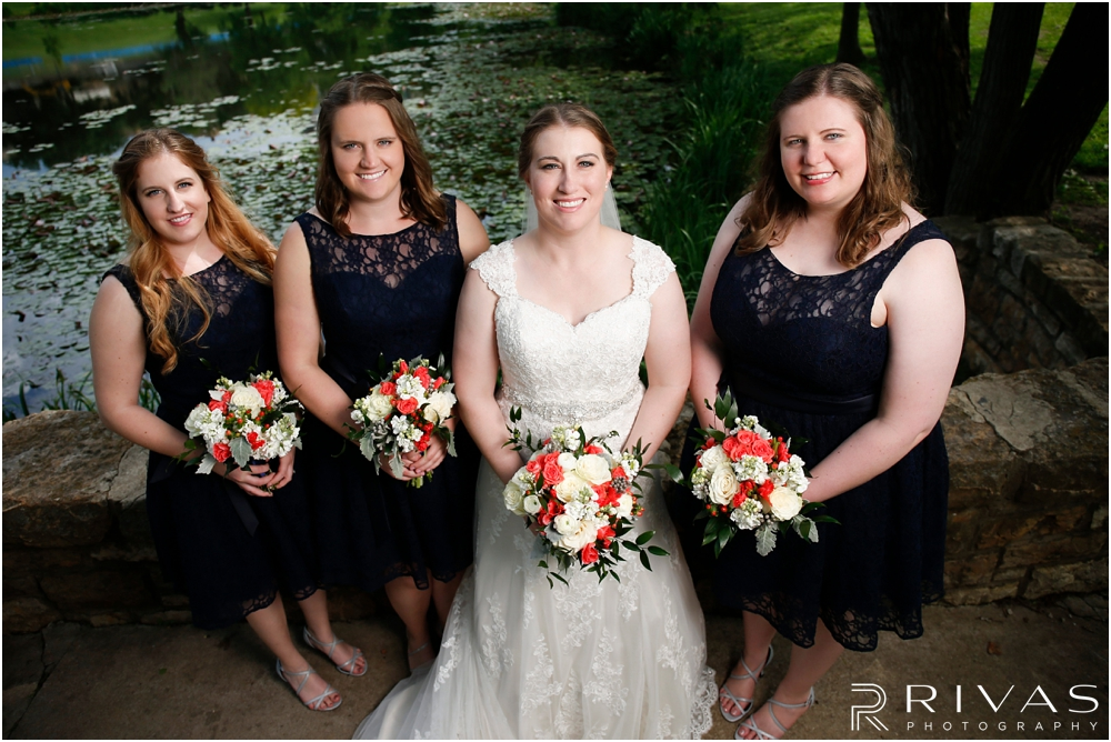St. John the Evangelist Catholic Church Spring Wedding | A formal picture of a bride and her bridesmaids standing on the stone bridge at Potter Lake in Lawrence, KS.